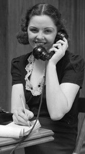 1930s Woman Receptionist Secretary Sitting At Desk In Office Talking On Telephone